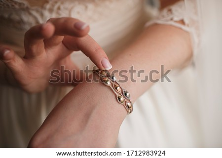 The bride dresses a gold bracelet with jewelry. The bride in a white wedding dress. Morning of the bride