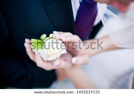 the bride gently touches the boutonniere in the breast pocket of the groom