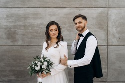 The bride is dressed in a white wedding dress with a wedding bouquet of white peony roses and eucalyptus leaves in her hands is waiting for the groom . The first meeting of the bride and groom