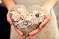 The bride is holding a pillow for the rings in the heart in the style of rustic