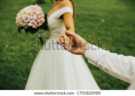 The bride leads the bridegroom, and he follows her. Just married. Stylish Romantic couple against the background green grass. Follow me. Bride holds the wedding bouquet with white and pink flowers. ストックフォト ©