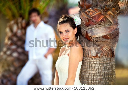 the bride near a palm tree and the groom in the distance. newly married celebrating their honeymoon