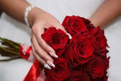 the bride's fingers are holding a bouquet of red roses against the background of a white dress, on the fingers is a French manicure, a sparkling bracelet on her hand. lmage with selective focus
