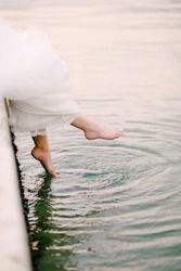 The bride sits on the pier and dangles her bare feet in the water, the legs peek out from under the wedding dress