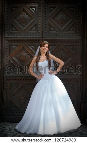 The bride standing  near the old door. - stock photo
