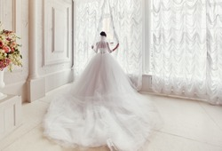 The bride stands at the window in a dress with a long train and veil.
