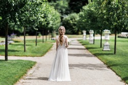 The bride stands with her back to the camera. Holds a bouquet. On the sidewalk.