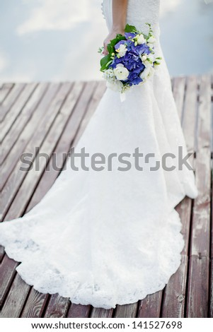 the bride with a bouquet from blue and white flowers; wedding concept