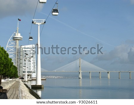 The bridge over the river tagus the observation tower Vasco da Gama and a cable car in Lisbon in Portugal
