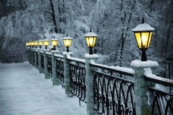 The bridge with beautiful lanterns, the fine snow evening in mountains