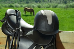 The bridle, the horse saddle and the riding helmet are in outdoors.