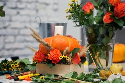 the bright autumn arrangement of flowers and berries in the pumpkin