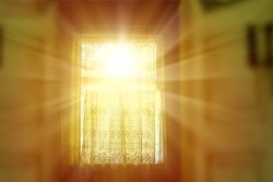 The bright rays of the sun illuminate the room through the old window of the village house.