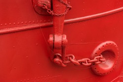 The bright red iron hull of a cargo ship docked in New York City