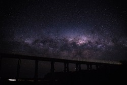 The bright starey universe in all it's cosmic beauty, over a wooden bridge built over a sandy beach.