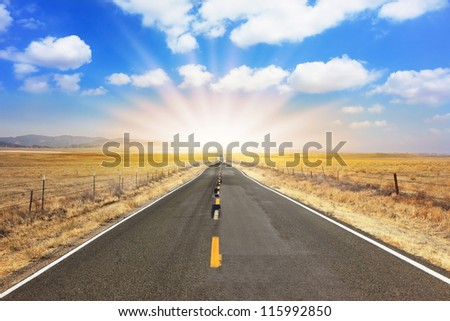 The bright sun illuminates the ideal road. The magnificent equal highway through boundless to the desert - stock photo