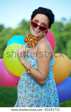 The bright woman in sunglasses with balloons and candy