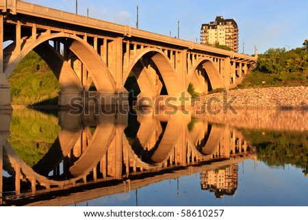 The Broadway Bridge in Saskatoon reflecting in the calm waters of the Saskatchewan River.