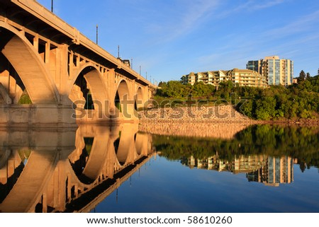 The Broadway Bridge in Saskatoon reflecting in the calm waters of the Saskatchewan River.