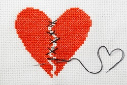 The broken heart is embroidered with red threads on a white canvas. Two halves sewn with black threads.