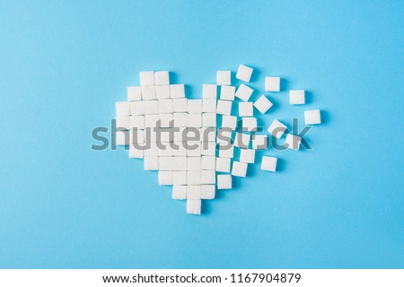 The broken heart made of cubes of sugar on a blue background