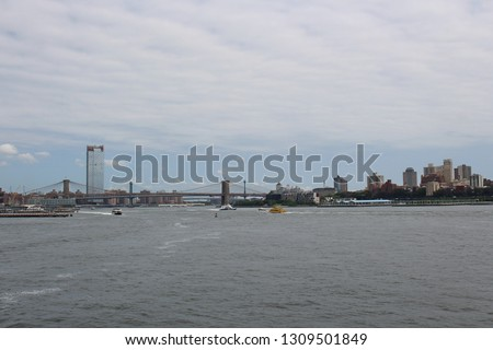 The Brooklyn and Manhattan Bridges with water taxis and tour boats cruising the Hudson River, New York City, USA