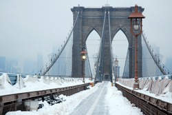 The Brooklyn Bridge is covered under a blanket of snow on a Winter's day