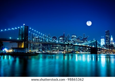 The Brooklyn Bridge lit up at night and the downtown Manhattan skyline under a full moon