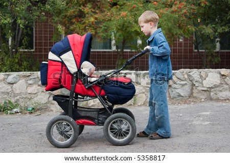 The brother rolls the younger sister in a pram.