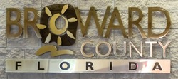 The Broward County logo sign made of brass and metal steel for the County Commissioners and the public in the lobby at 115 S. Andrews Avenue Fort Lauderdale Florida on a faux brick block textured wall