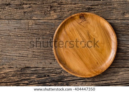 The brown wooden plate on a rustic table closeup. Top View with Copy Space for Text, wooden background. - Shutterstock ID 404447350