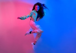 The brunette dances in neon, the dancer in red-blue. Hip hop girl, party, smile. Model in flight, jumping.