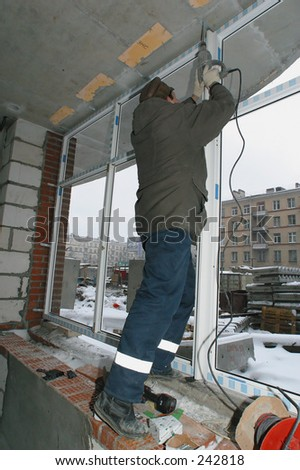 The builded house. Worker establishing window frames.  *** Local Caption *** Editorial, No Release Required