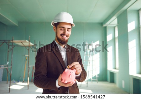 The builder foreman is holding a piggy bank in his hand.