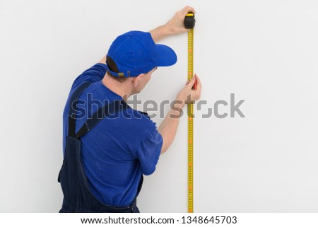 The builder measures the distance on a white wall with a tape measure