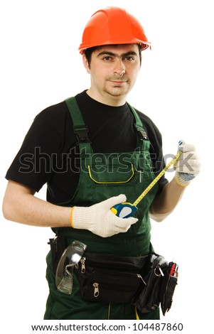 The builder measures the length of the tape measure on a white background.