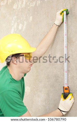 The builder measures the length of the tape measure on the background of a concrete wall