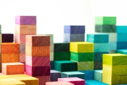 The building blocks. Spectrum of stacked multi-colored wooden blocks with white space above. Background or cover for something growing, rising, increasing, or building up.