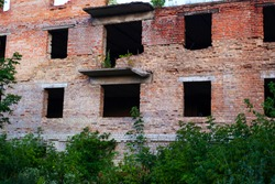 the building of a supermarket on Donbass fired and destroyed by heavy armament is a red brick building damaged by an explosion. military actions