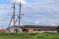 The building of an abandoned cowshed and pillars without wires near it