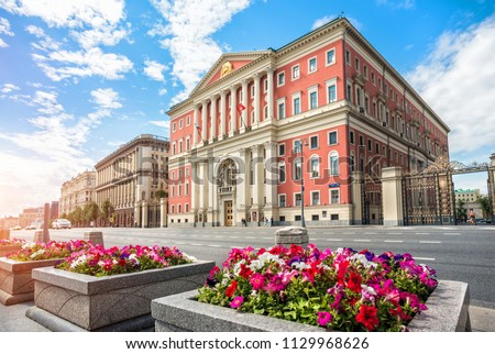 The building of the Moscow Government on Tverskaya Street and colorful flowers on a summer sunny morning park