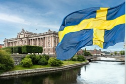 The building of the Swedish Parliament (Riksdag) and the Riksbank Bridge over the Lilla Vartan Strait with the national flag of Sweden in the foreground.