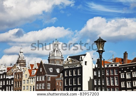 The buildings and the dome of St. Nicholas Church in Amsterdam, the clouds on blue sky