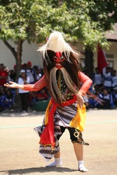 The Bujang Ganong mask is bright red with characteristic bulging eyes, a large nose, and protruding teeth. The mask is made of dadap wood, while the hair on the mask is made of a pony tail.