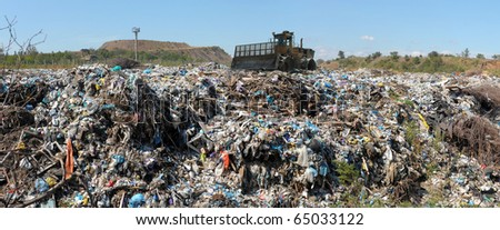The bulldozer buries food and industrial wastes - stock photo