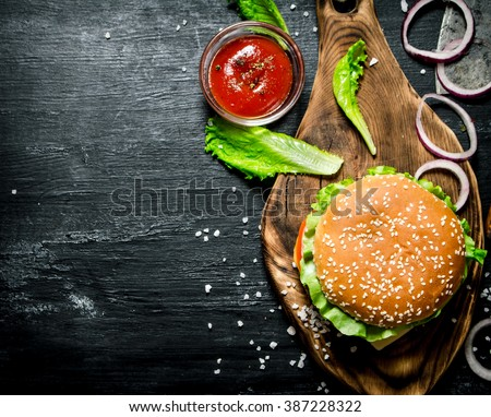The Burger and the fresh ingredients on the old Board. On a black chalkboard.  Top view.