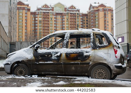 The burnt down car in snow. The second day after a fire.