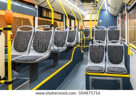 The bus inside. Grey seats and yellow handrails