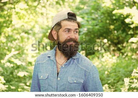 The bushy beard is great. Happy caucasian guy with beard on natural background. Bearded man smiling with stylish mustache and beard shape. Unshaven hipster with textured beard hair on summer outdoor.