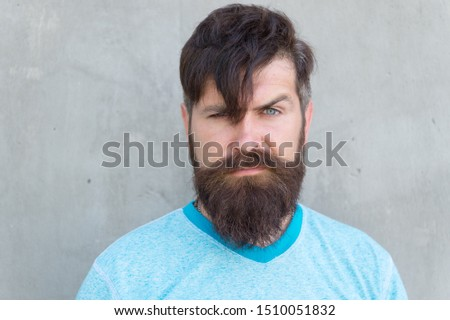 The bushy mustache is great. Bearded man with stylish mustache shape. Brutal hipster with textured mustache hair on unshaven face. Serious guy wearing long beard and mustache on grey wall.